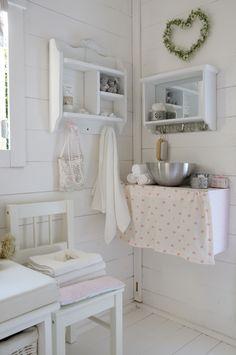 """Ha det på badet """"Baderomsmøblet"""" er en gammel trekasse som er malt hvit. Det rosa blomstrede forhenget skjuler ting og tang. Det lille speilet med praktiske kroker er fra Jysk."""
