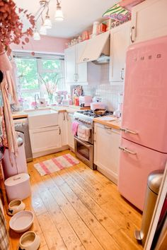 white and pink kitchen with vintage style refrigerator and stainless steel appliances is so charming!