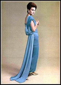 Model in two shades of blue jersey draped in falling panels in back by Pierre Balmain, jewelry by Cartier, photo by Pottier, 1961