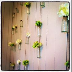 Flowers in bottles hanging on the wall at Hamptons Home Living, Paddington. Love!
