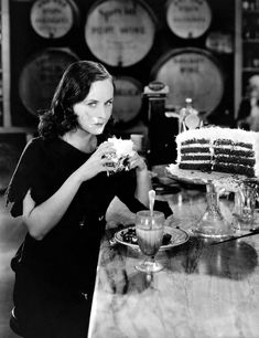 1936: American actress Paulette Goddard (1911 – 1990) sits in a cafe and gorges herself on cake and soft drinks in a scene from 'Modern Times', directed by Charles Chaplin. (Photo by Max Munn Autrey)