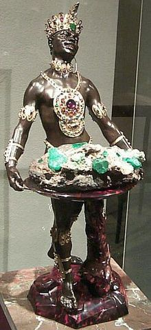 """One of the finest examples of a blackamoor in the arts is the Mohr mit Smaragdstufe (""""Moor with Emerald Cluster""""), in the collection of the Grünes Gewölbe in Dresden, Germany. It was created by Balthasar Permoser in 1724. The statue is richly decorated with jewels and is 63.8 cm (2.09 ft) high."""