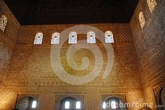 Photo taken inside the Alhambra in Granada in Spain. In the picture you see three walls and the ceiling, made of dark wood, one of the great halls of the Alhambra. On the walls decorated open top five windows with stained glass windows that equal those with twins, but more small and deep, placed at the bottom leading light in the room.