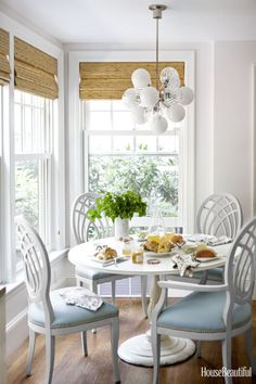 Interior decoratorLaura Church Wilmerding paired a pedestal table from her childhood home with vintage dining chairs she found at the Stamford Antique & Artisan Center and had covered in S. Harris's Pivotal. The1960s-style light fixture isPerle by Oggetti.