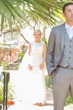 Bride in sleeveless wedding dress sneaks up on groom for first look.