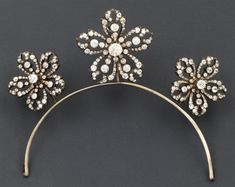 A French diamond floral tiara,circa 1875,featuring three flower heads, each with five petals arranged on a platinum band.