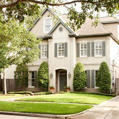 gray shutters and trim on white house with keystone windows and traditional manicured garden.