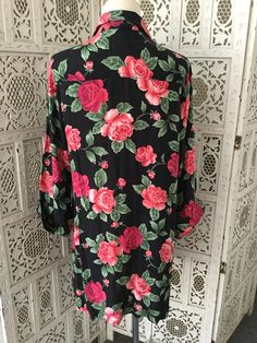 90s Floral Rose Print Tunic Top or Dress with long sleeves and button front. Soft and flowy rayon fabric with large sized magenta red-pink roses iconic of the 90s. Rose print has brushes of medium and light pink--very pretty! Styems and leaves are mossy green colors.  Structured style with collar and white pearlized buttons. Versatile item-- can be worn buttoned as dress or tunic top, or open as light jacket or cardigan. Very soft fabric that drapes well and flutters when you move. Can be…