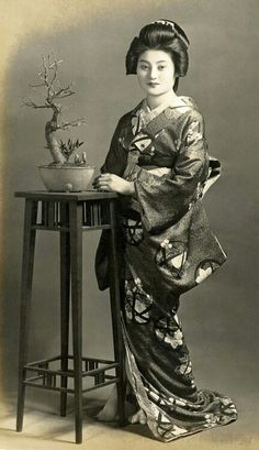 This vintage postcard from around the 1930s shows a Geiko (Geisha) standing beside a jardinière stand with a bonsai tree in bud.