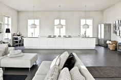 Industrial style room with kitchen in white and adjacent lilving room via Expensive Life