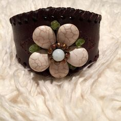 Leather Flower Bead Cuff Leather Flower Bead Cuff - All brown leather cuff with whip stitching detail on the edges. Top of cuff is accented with a beaded flower. Cuff just slides on to the wrist and then press both sides together to tighten it, or pull apart to loosen it up. Excellent condition! Jewelry Bracelets