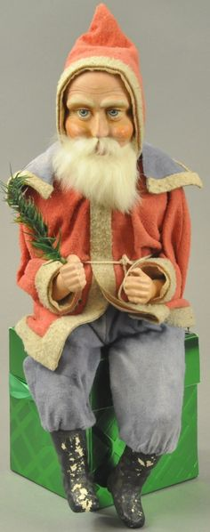 """Germany, a large seated Santa, composition legs and hands, wonderful kind looking composition face with rabbit fur beard, dressed in red felt robe with blue cape, holding feather tree sprig, a truly rare find. 15"""" seated. (VG - Exc. Cond.)"""