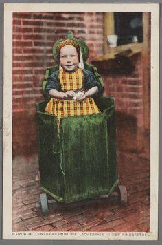 BUNSCHOTEN-SPAKENBURG LACHEBEKJE IN DEN KINDERSTOEL. 1900-1930.  Kindje met klapmuts, jurkje en fries schort in Spakenburgse kinderstoel (kakstoel) op wieltjes voor het huis. #Utrecht #Spakenburg