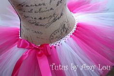 BASIC 4 Color Tutu In Fuchsia, Shocking Pink, Light Pink and White in Shadow Pattern. This is the perfect pattern for trail runners who love nature and frolicking in the woods. You will look pretty in pink for the Race for the Cure or any other Breast Cancer Awareness run or event. Choose a bow in any color. RUN LIKE A GIRL. This BASIC 4 color tutu is made from 100% Nylon tulle. Two layers of tulle make this tutu full and fluffy which means your tutu won't look wimpy or deflated by the end…