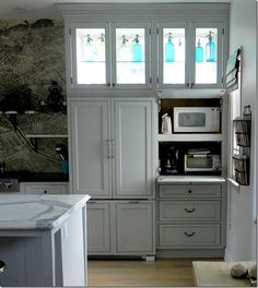 high windows behind the cabinets let light in. LOVE how the toaster oven, etc is hidden but easily accessed. The paint colors:  BM White Wisp-kitchen walls  BM Sea Haze- Pantry door  BM Revere Pewter- window trim  BM Sea Star - Dutch Door  BM FieldStone - Family room