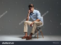 Pensive brunette man in blue shirt sitting on the chair over grey background