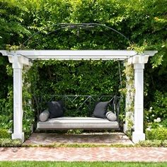 Hanging swing under a pergola with climbing flowers nestled in a garden. The perfect reading spot