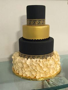 29 Luxurious Black And Gold Wedding Ideas   Glitter Weddings     Black  gold  and ivory wedding cake with ruffled base and gold lace  Ideal  for a Gatsby party too