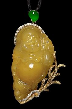 A jadeite Buddha pendant The pendant set with a yellow jadeite, measuring approximately 52.0mm x 29.9mm, carved as a laughing Buddha holding a lingzhi, the frame of a realistically textured and modelled branch with diamond accents, all suspended from a pear-shaped cabochon jadeite, the diamonds estimated to weigh approximately 0.49 carats in total, length 6.7cm