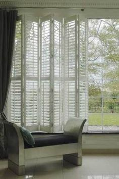 not bi-fold, but hex-fold  Shutters; wonder if they are on a track or not? AND, with curtains but not in a recessed window