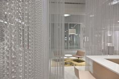 Swiss architecture firm Burkard Meyer knew only an innovative and unique space would do in the new showroom of bathroom fixture company Talsee. Partnering with KriskaDECOR, a family run business that cranks out metallic chain curtains, a modular system of rain-like silver chains were created to hang in the central client reception area of the space.