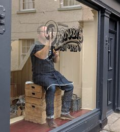 Signwriting black outlines on a gold leaf window sign for Parnaby's Saddlery in Malton, North Yorkshire.