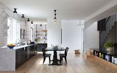 Open concept kitchen with industrial elements like schoolhouse pendant lights and simple custom cabinetry.