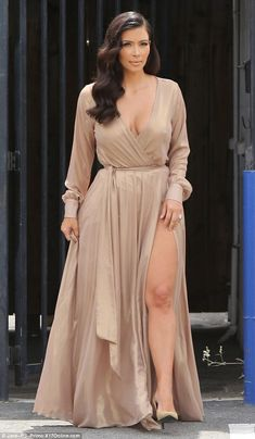 Sizzling appeal: Kim Kardashian worked some more of her magic in a buff-coloured wrap-around gown with thigh-high slit in the skirt for a photo shoot in LA on Sunday