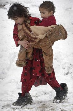 iseo58: An Afghan refugee girl carries her sister around their camp during a snowstorm