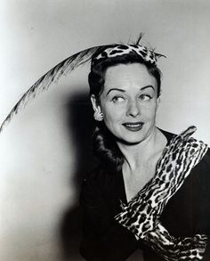 Dangerous Leopard is the name that New York celebrity milliner, Mr John, gave to the ensemble of leopard skin and feather hat with matching gloves worn by actress Paulette Goddard in this photograph. The photograph is one of four promotional photographic prints for Mr John's Romance in Venice fall and winter collection of 1953.