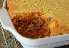 This tamale pie recipe is filled with seasoned ground beef, garlic, onions, corn and tomatoes and baked to perfection with a cheesy cornmeal crust.