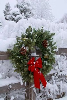 Christmas wreath on snowy fence; looks just like our driveway fence on the farm.