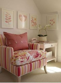 Sarah Richardson Pink art in Ikea ribba frames, pink painted accent side table with drawer, upholstered stripe pink chair with upholstered flower print pink cushion, white pink red polka dot pillow with buttons and wall to wall beige tan sand carpeting.