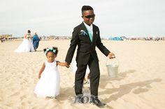Ring bearer in tux helps flower girls during beach wedding processional at the Ocean City, MD inlet:  https://www.roxbeachweddings.com/
