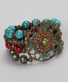 Opt for a wrist piece with ornamental flair. This antique-chic bracelet fits the bill thanks to its enameled filigree medallion and stretchy strands of earthy, semiprecious-inspired beads.
