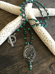 Gorgeous turquoise and detailed pewter beads are crocheted onto dark brown nylon cord featuring a stunning artisan handcrafted pewter mermaid