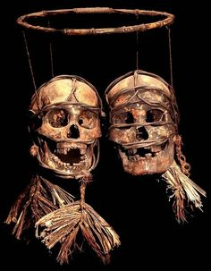 Dayak Tribe: Two hanging bound and decorated headhunted human trophy skulls.