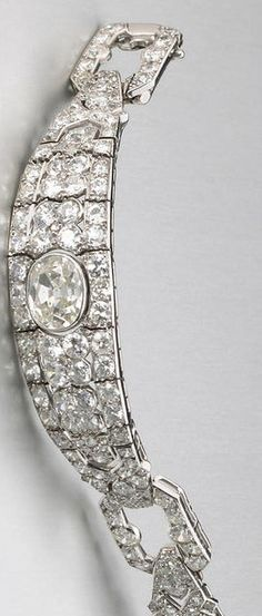An art deco diamond and platinum bracelet, French, Cartier, circa 1925 designed as two lozenge-shaped panels, each of openwork design, set throughout with old European-cut diamonds and separated by diamond-set buckle style links, one panel centering a larger oval-shaped diamond; signed Cartier Paris; with French assay marks; oval-shaped diamond weighing an estimated: 2.00 carats; remaining diamonds weighing an estimated: 18.00 carats; length: 6 7/8in.