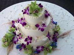 Three tier tropical white buttercream wedding cake decorated with purple Hawaiian flowers and green Cymbidium orchids
