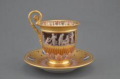 Tasse d'époque Charles X en porcelaine de Sèvres à décor doré mat et brillant de rinceaux et frise de putti en grisaille rehaussé de cabochons améthyste et médaillon de profile à l'antique sur fond bleu en trompe l'oeil et en rappel sur la coupelle, h. 12 cm