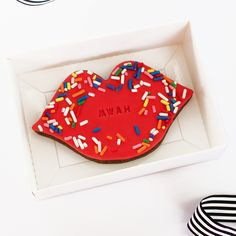 Delicious handcrafted chocolate sugar cookies.  Cool lips chocolate biscuit made with the finest ingredients, with rainbow sprinkles and embossed MWAH. Beautifully packaged in a white gloss gift box with a black and white stripped ribbon. #lips #lipcookie #kiss