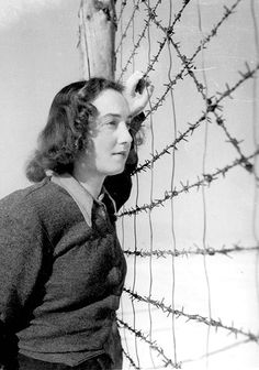 Yalina Lebovicova standing by the barbed wire in the Nováky forced labor camp, Slovakia. Yalina was an actress in the camp's theater. From the photo albums documenting the forced labor of Jews in Slovakia. These albums were compiled for the Slovakian authorities by the Jewish Center in Bratislava