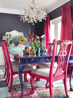 A bold blue dining table, hot pink chairs and a crystal chandelier for a vibrant space