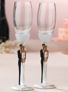 "This pair of glasses is unique for the slender, tall design of its stem. The glass is held by a resin stem and base. Accenting the stem is a painted resin bride and groom in loving embrace. Stands 10"" tall. Matches the wedding topper..."