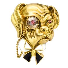 "Van Cleef and Arpels: ""The Toff"" bulldog pin, designed as a whimsical, British bulldog, analogous to Winston Churchill, with white enameled wingtip collar and black enameled bow tie, circular-cut ruby eyes and gold chained, circular-cut diamond monocle, mounted in 18k yellow gold, with double pin stem in 18k yellow gold at back."
