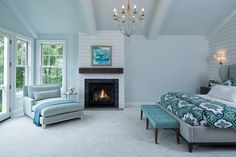 bedroom with soft blue painted wall, white horizontal wood paneled wall, blue ceiling with white wood beams, blue rug, blue lounge chair, blue bench, white bedding, blue cover, fireplace of Good Sleep in a Beach Theme Bedroom
