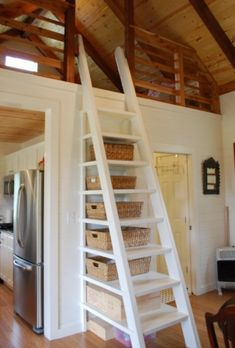 a sleeping loft off the kitchen, with a ladder that has built in storage,