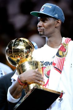 Chris Bosh #1 of the Miami Heat celebrates with the Larry O'Brien Finals Championship trophy after they won 121-106 against the Oklahoma City Thunder in Game Five of the 2012 NBA Finals on June 21, 2012 at American Airlines Arena in Miami, Florida.