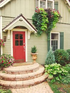 This small home's color scheme is charming - the soft understated light green siding, white trim, and dark green shutters provide the perfect backdrop for the red front door - talk about inviting! We (Diy Step Front Door) Green Siding, Green Shutters, White Siding, Exterior Paint Colors, Exterior House Colors, Craftsman Exterior Colors, Exterior Siding, Light Green House, Front Porch Steps