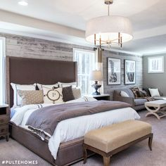 A bedroom designed with more than just shut-eye in mind! The Owner's Retreat area, large pendant light, rustic shiplap walls and bench at the end of the bed create an inviting living space. | Pulte Homes